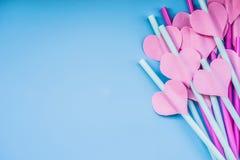 Vacances de Saint Valentin rose lumineux et pailles à boire bleues avec des coeurs et un ruban rose sur le bleu pailles sirotante Photo libre de droits