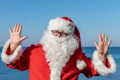 Vacances du ` s de Santa en mer Équipement rouge traditionnel et détente sur la plage image libre de droits