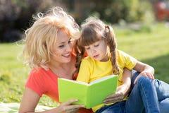 Vacances en nature Fille de mère et d'enfant ayant l'amusement sur la pelouse image libre de droits