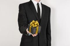 Vacances et cadeaux de thème : un homme dans un costume noir juge le cadeau exclusif enveloppé dans une boîte noire avec le ruban Photo libre de droits