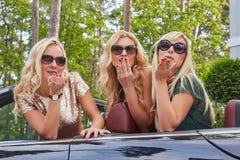 Vacances et concept de personnes Trois amis féminins blonds heureux portant les vêtements à la mode dans des lunettes de soleil f Photos libres de droits
