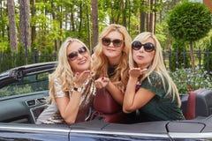 Vacances et concept de personnes Trois amis féminins blonds heureux portant les vêtements à la mode dans des lunettes de soleil f Image stock