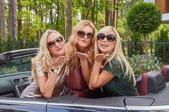 Vacances et concept de personnes Trois amis féminins blonds heureux portant les vêtements à la mode dans des lunettes de soleil f Images stock