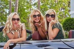 Vacances et concept de personnes Trois amis féminins blonds heureux portant les vêtements à la mode dans des lunettes de soleil f Photo stock