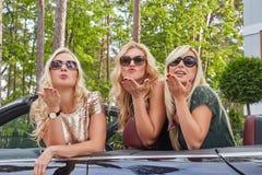 Vacances et concept de personnes Trois amis féminins blonds heureux portant les vêtements à la mode dans des lunettes de soleil f Photographie stock libre de droits