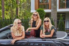 Vacances et concept de personnes Trois amis féminins blonds heureux portant les vêtements à la mode dans des lunettes de soleil s Images libres de droits