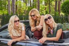 Vacances et concept de personnes Trois amis féminins blonds heureux portant les vêtements à la mode dans des lunettes de soleil s Photo libre de droits