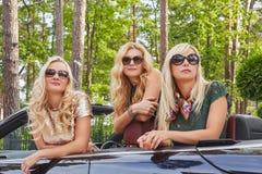 Vacances et concept de personnes Trois amis féminins blonds heureux portant les vêtements à la mode dans des lunettes de soleil s Photos libres de droits