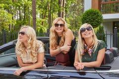 Vacances et concept de personnes Trois amis féminins blonds heureux portant les vêtements à la mode dans des lunettes de soleil s Image stock