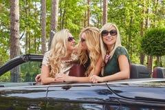 Vacances et concept de personnes Trois amis féminins blonds heureux portant les vêtements à la mode dans des lunettes de soleil s Photos stock