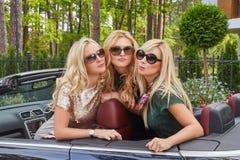 Vacances et concept de personnes Trois amis féminins blonds heureux portant les vêtements à la mode dans des lunettes de soleil s Photographie stock