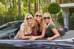 Vacances et concept de personnes Trois amis féminins blonds heureux portant les vêtements à la mode dans des lunettes de soleil s Images stock