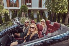 Vacances et concept de personnes Trois amis féminins blonds portant les vêtements à la mode dans des lunettes de soleil se reposa Photographie stock