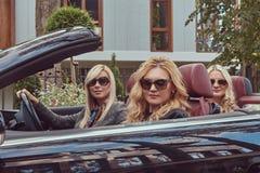 Vacances et concept de personnes Trois amis féminins blonds portant les vêtements à la mode dans des lunettes de soleil se reposa Photographie stock libre de droits
