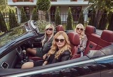 Vacances et concept de personnes Trois amis féminins blonds portant les vêtements à la mode dans des lunettes de soleil se reposa Images libres de droits