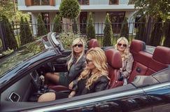 Vacances et concept de personnes Trois amis féminins blonds portant les vêtements à la mode dans des lunettes de soleil se reposa Image libre de droits