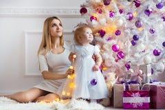 Vacances heureuses de famille La fille de mère et d'enfant dans la pièce décorée par Noël célèbrent Noël et la nouvelle année Images libres de droits