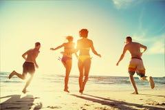 Vacances heureuses de plage de coucher du soleil de course d'amis Photo stock