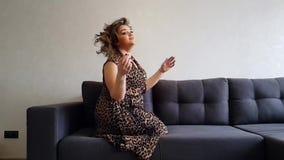 Vacances heureuses de robe de pleine fille sur le divan clips vidéos