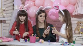 Vacances heureuses Une mère et ses filles peignent des oeufs Famille se préparant à Pâques Les filles mignonnes de petits enfants banque de vidéos