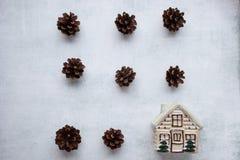 vacances, hiver et concept de célébration - composition en Noël cônes de pin, maison de jouet sur le fond de ciment Configuration photo stock