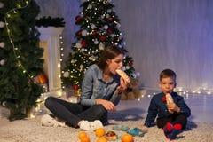 Vacances ouvertes de nouvelle année d'arbre de Noël de cadeaux de Noël de maman et de jeune garçon images stock