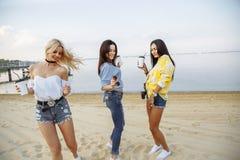 Vacances partie de plage Groupe de jeunes femmes heureuses dansant à la plage sur le coucher du soleil d'été Photographie stock libre de droits