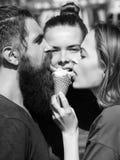 Vacances, suivre un régime, refroidissant Amis mangeant le cornet de crème glacée savoureux Image stock