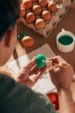 Vacances, tradition et concept de personnes - fin des mains de l'homme colorant des oeufs de pâques avec la brosse image libre de droits