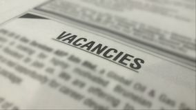 Vacancies ads on a newspaper with blurred surrounding royalty free stock photography