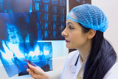 The vacancies for Doctors. Young female doctor standing at the table with X-ray,photography Royalty Free Stock Photo