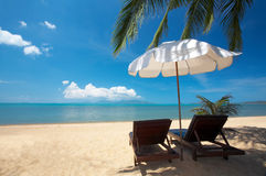 Vacancy. View of two chairs and  white umbrella on the beach Royalty Free Stock Photography