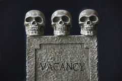 Vacancy. A terrifying trio of skulls invites you for a stay. There's a vacancy if you dare. Great Halloween image and also a useful conceptual image for smoking royalty free stock photo