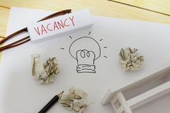 Vacancy and employment concept. White paper with drawing of a light bulb, crumpled papers, glasses, pencil, mini toy table and word VACANCY written on a small stock photo