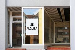 Spanish vacancy sign in empty shop window reads se alquila meaning for rent. Vacancy sign in spanish shop or store window reads se alquila which translates as stock images