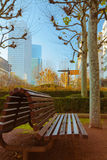 Vacant bench in a business area with skyscrapers and blue sky in Stock Photography