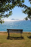 Vacant bench. A vacant bench perfectly placed for a beautiful view out to sea with islands in the distance on a summers day Stock Images