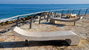 Vacant benches on vacant shore. Vacant benches are waiting to their visitors on the Mediterranean seashore at one early sunny morning stock photos