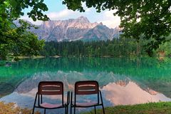 Vacant Chairs admiring fusine lakes landscape italy. Vacant Chairs admiring fusine lakes reflection landscape italy royalty free stock image