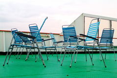Vacant Deck Chairs. Vacant blue deck chairs in haphazard setup, on green floor covering, sitting on exterior of a building royalty free stock photos