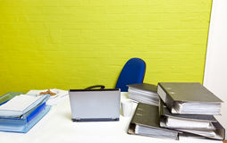 Vacant desk with laptop, folders and empty chair Stock Image