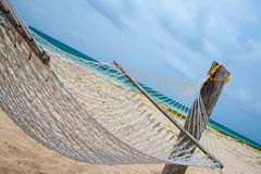 Vacant hammock on a tropical beach. Empty hammock on a tropical beach with the Caribbean ocean in the background waiting for someone to lay back and relax Royalty Free Stock Photo