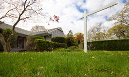 Vacant House. A low down view of a vacant house with a signpost on the lawn Stock Photography