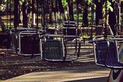 Vacant merry-go-round seats taken closeup. Toned image Stock Photos
