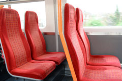 Vacant red seats in a train. Vacant passenger seats in a train traveling through the suburbs of London Royalty Free Stock Images