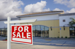 Vacant Retail Building with For Sale Real Estate Sign. In Front royalty free stock photography