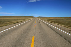Vacant Road. Looking straight down the vanishing point of a vacant country road with blue sky and yellow dashed lines Stock Photos