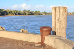 Vacant rusty metal mooring bollard at the pier with ocean backgr Stock Photography