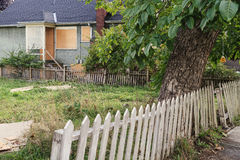Vacant unkept yard with rickety fence and boarded up house Royalty Free Stock Images