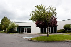 Vacant White Office Building and Lot. A vacant modern white office building and empty parking lot with nice landscaping Stock Photos